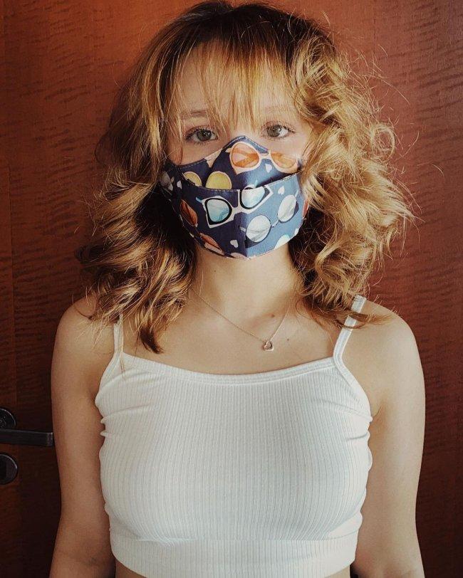 Larissa Manoela usando máscara de proteção azul com detalhes coloridos, regata branca, colar e cabelo curto.