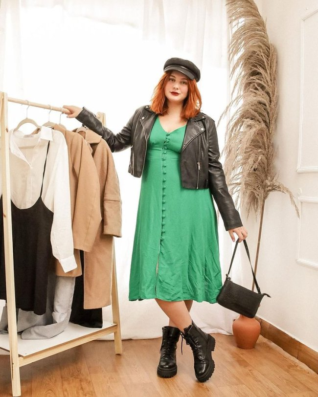 Jovem posando ao lado de arara de roupas, usando boina preta, vestido verde, bolsa preta, coturno preto, e o com expressão séria.