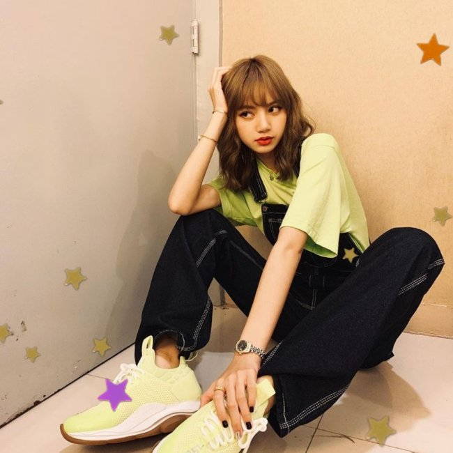 Lisa, integrante do grupo Blackpink, sentada com uma das mãos tocando seu pé e a outra apoiada na cabeça; com uma expressão pensativa;usando camiseta verde clara, assim como seu tênis e calça jeans.