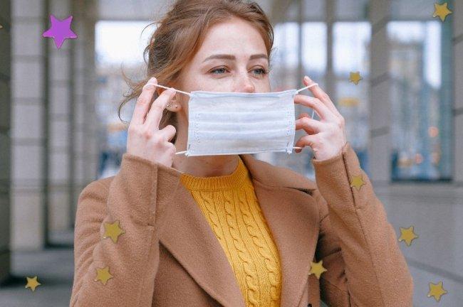 Jovem colocando máscara branca de proteção, com expressão séria, usando blazer marrom e blusa de lã amarela.