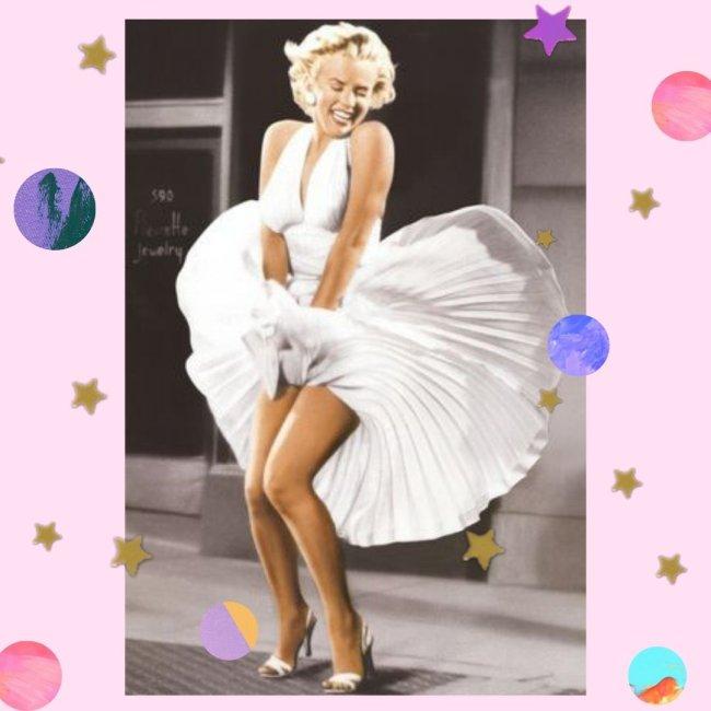 Marilyn Monroe com a barra do vestido voando, enquanto tenta segurá-la, sorridente.