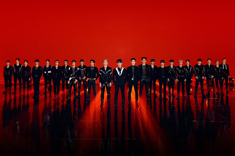 Supergrupo NCT em um fundo vermelho, os integrantes estão alinhados na diagonal formando uma espécie de triângulo com um integrante no meio; todos vestem roupas completamente pretas, algumas com detalhes brancos