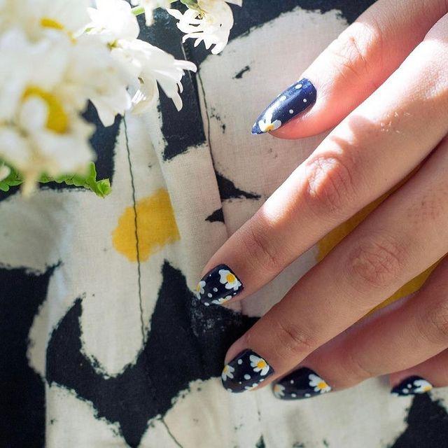 Mão mostrando os dedos com esmalte azul e flor branca com detalhe amarelo ao lado de um tecido que parece o desenho da unha.