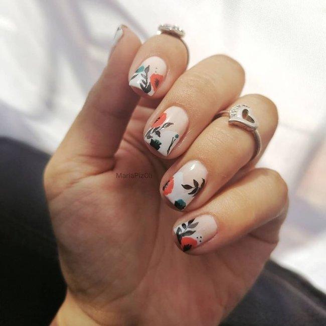 Dedos dobrados com anel exibindo nail art com base clara e detalhes laranja e preto.