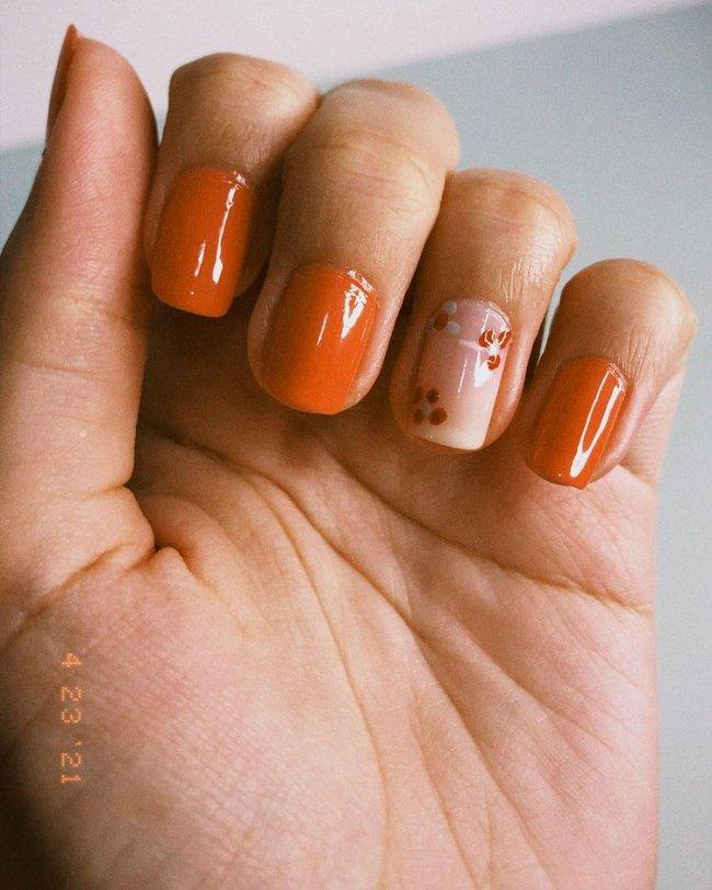 Mão com o dedo dobrado exibindo as unhas laranjas com uma com base clara e flores brancas e laranja.