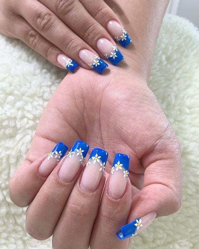 Duas mãos exibindo as unhas com base clara e francesinha azul com florzinha branca.