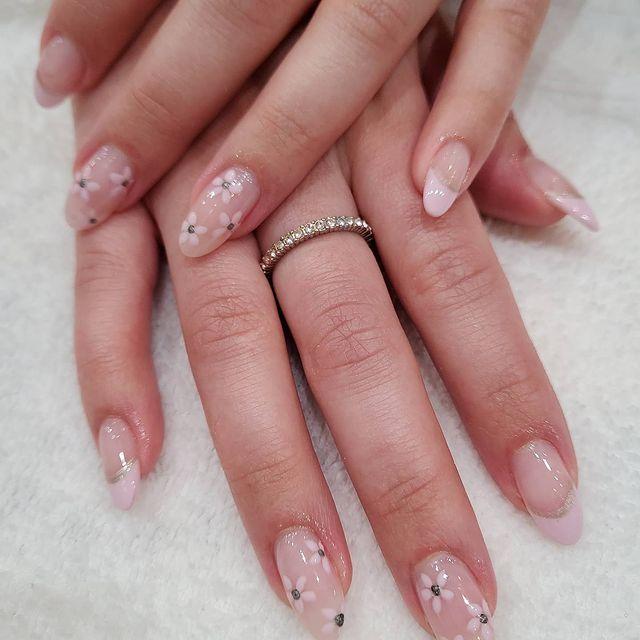 Mãos uma sob a outra, com um anel fininho, exibindo as unhas com francesinha delicada em tom nude e pequenas florzinhas brancas.