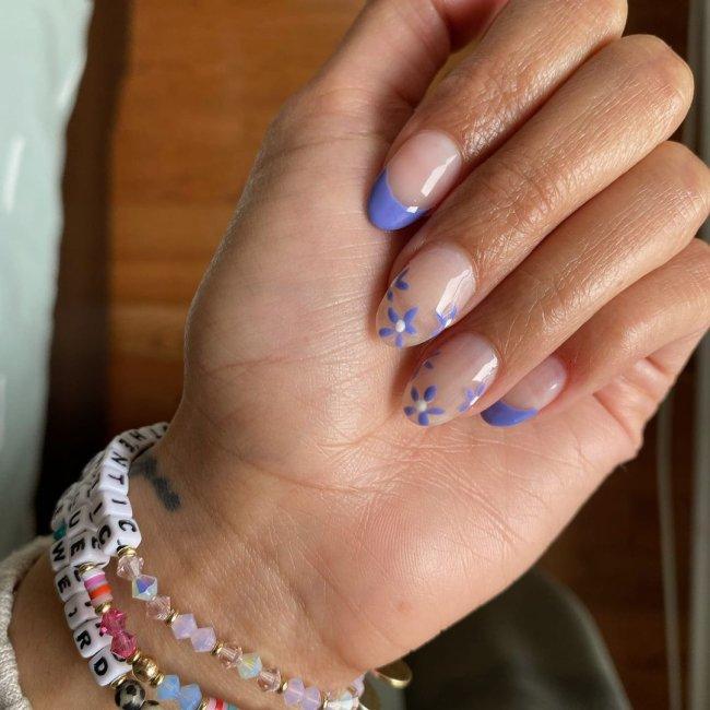 Mão com os dedos dobrados e pulseiras coloridas no pulso, exibindo as unhas com francesinha roxa e flores roxas.
