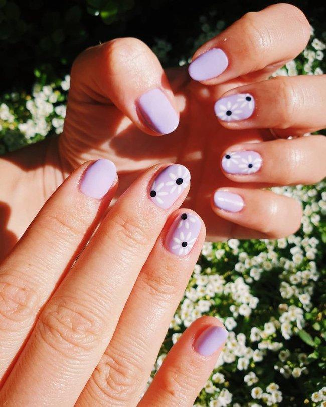 Nail art simples com florzinha em fundo lilás