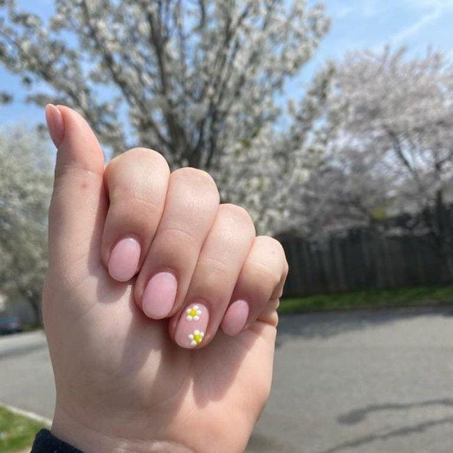Mão com os dedos dobrados exibindo as unhas com florzinha branca.