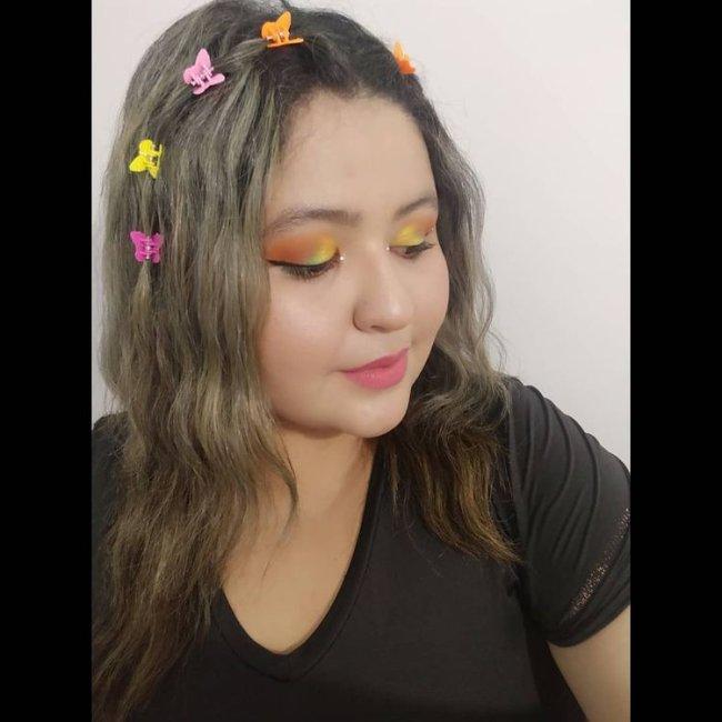 Jovem olhando para baixo com sombra amarela e laranja, usando presilha de borboleta na lateral do cabelo usando camiseta preta com uma expressão sorridente.