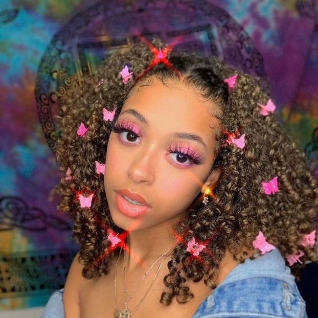 Jovem com sombra rosa, cabeça levemente inclinada e expressão séria, usando presilhas coloridas no cabelo.