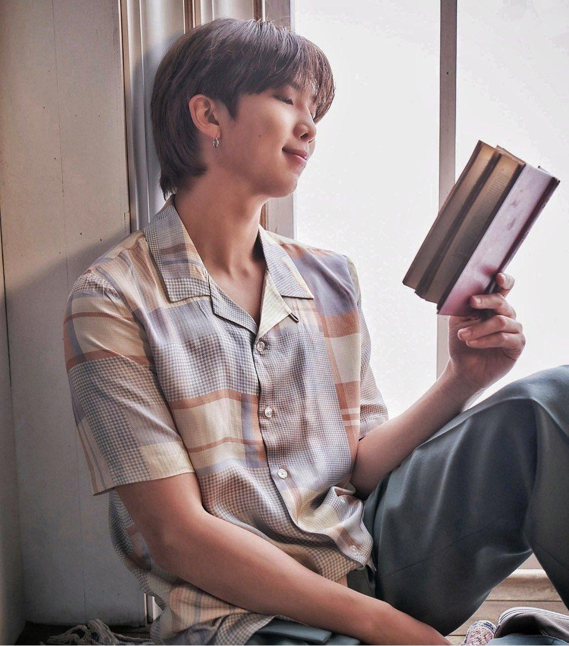 RM do BTS sentado em uma janela lendo um livro, ele segura o livro com apenas uma das mãos e a outra está apoiada na perna