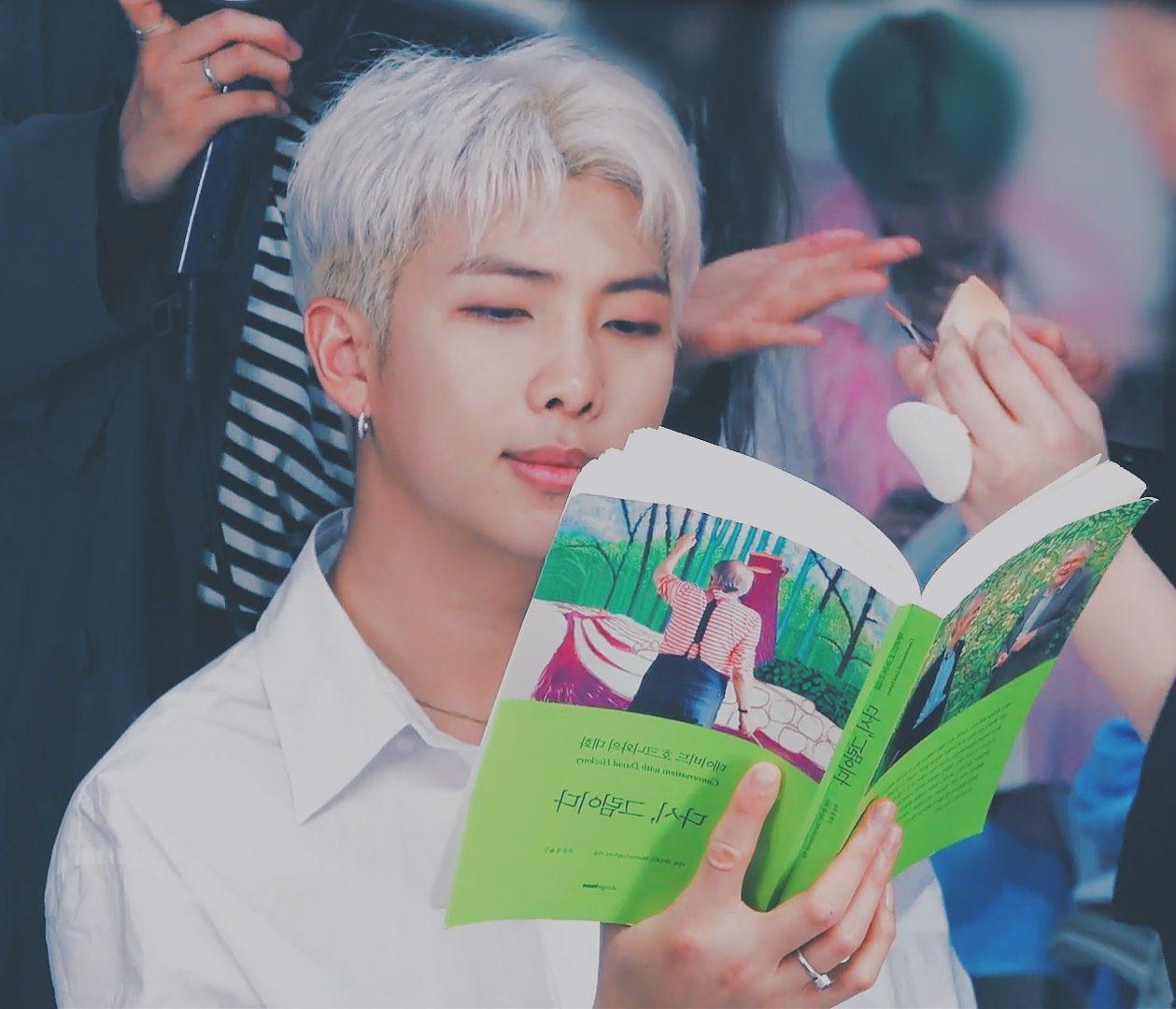 RMT lendo livro; ele usa uma camisa branca e seu cabelo está platinado, o cantor sorri levemente