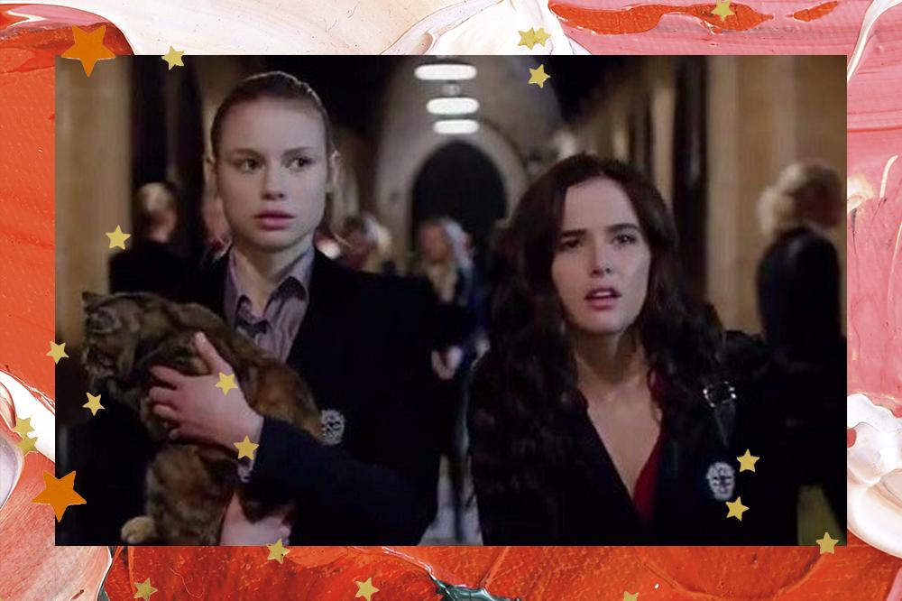 Lisa e Rose em filme de Academia de Vampiros; Lisa está segurando um gato com expressão surpresa e Rose está fazendo uma expressão confusa ao lado da amiga; as duas estão andando no corredor da escola; a borda da imagem é uma textura de tintas em tons de vermelho, rosa e branco com estrelas amarelas e laranjas como decoração