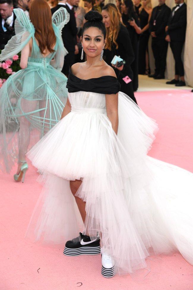 Foto da cantora e compositora Alessia Cara no tapete vermelho do Met Gala de 2019. Ela usa um vestido branco com detalhe preto no ombro e tênis de cores distintas, o da direita é preto com branco e do esquerda é branco com preto da Nike. Ela olha para a câmera e sorri.