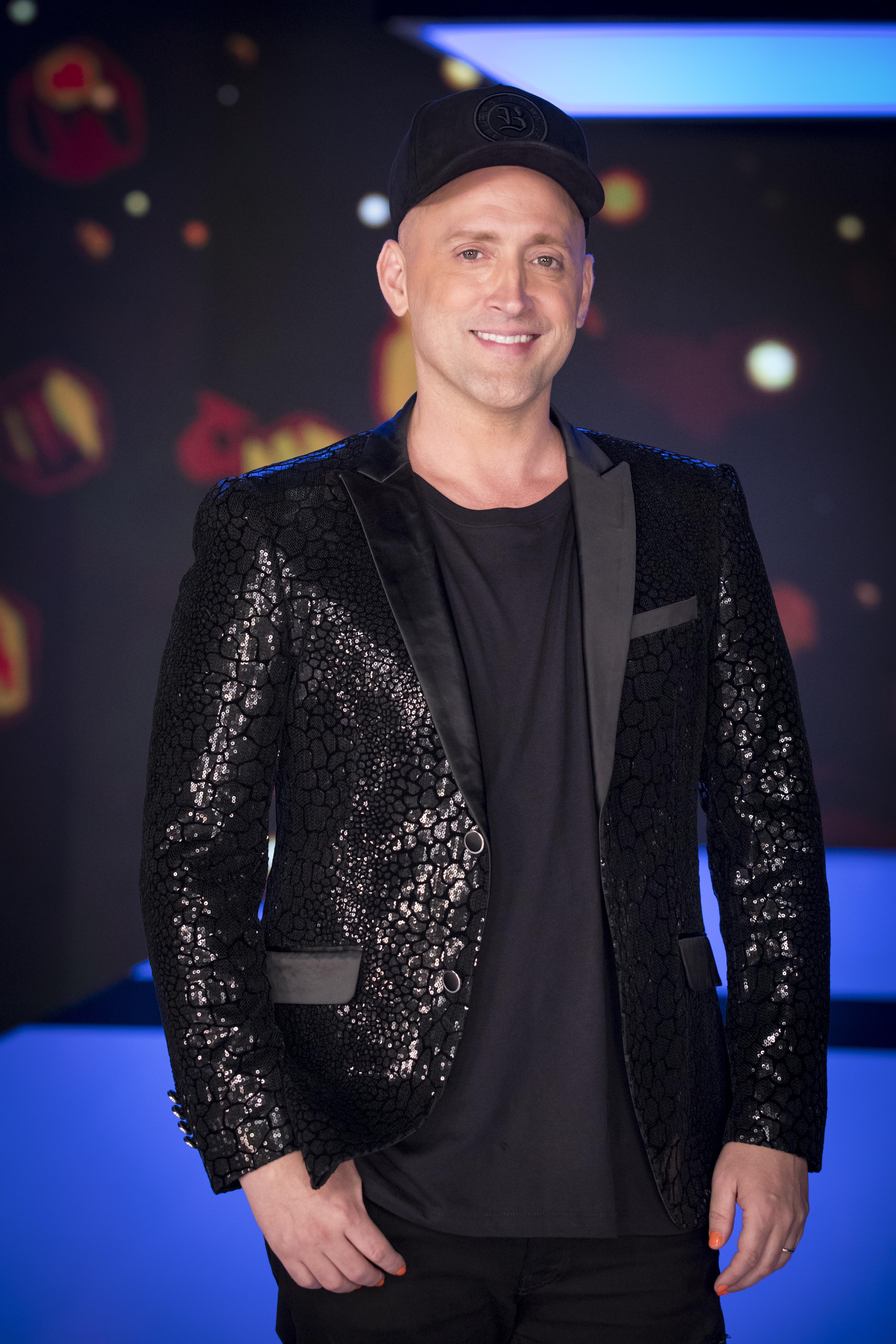 Paulo Gustavo sorrindo enquanto posa para foto vestindo roupas pretas e boné