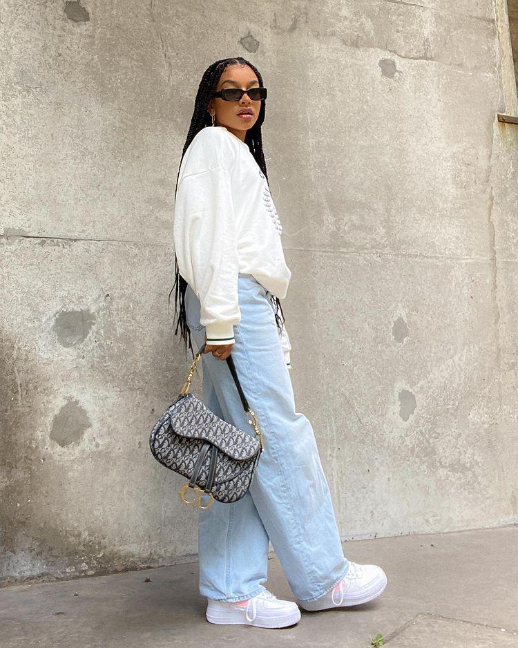 Foto de uma mulher em uma calçada. Ela usa um moletom branco, calça jeans baggy, tênis branca, shoulder bag e um óculos de sol vintage. Ela olha para a câmera e não sorri.