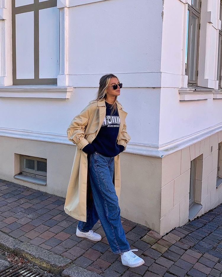 Foto de uma mulher na calçada andando. Ela usa um moletom azul baggy, calça jeans baggy e sobretudo bege. Ela não olha para a câmera e sorri.