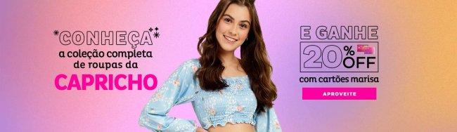 Ao centro, modelo usa cropped azul de manga comprida. Ela está com uma das mãos na cintura, sorrindo. De um lado, a frase