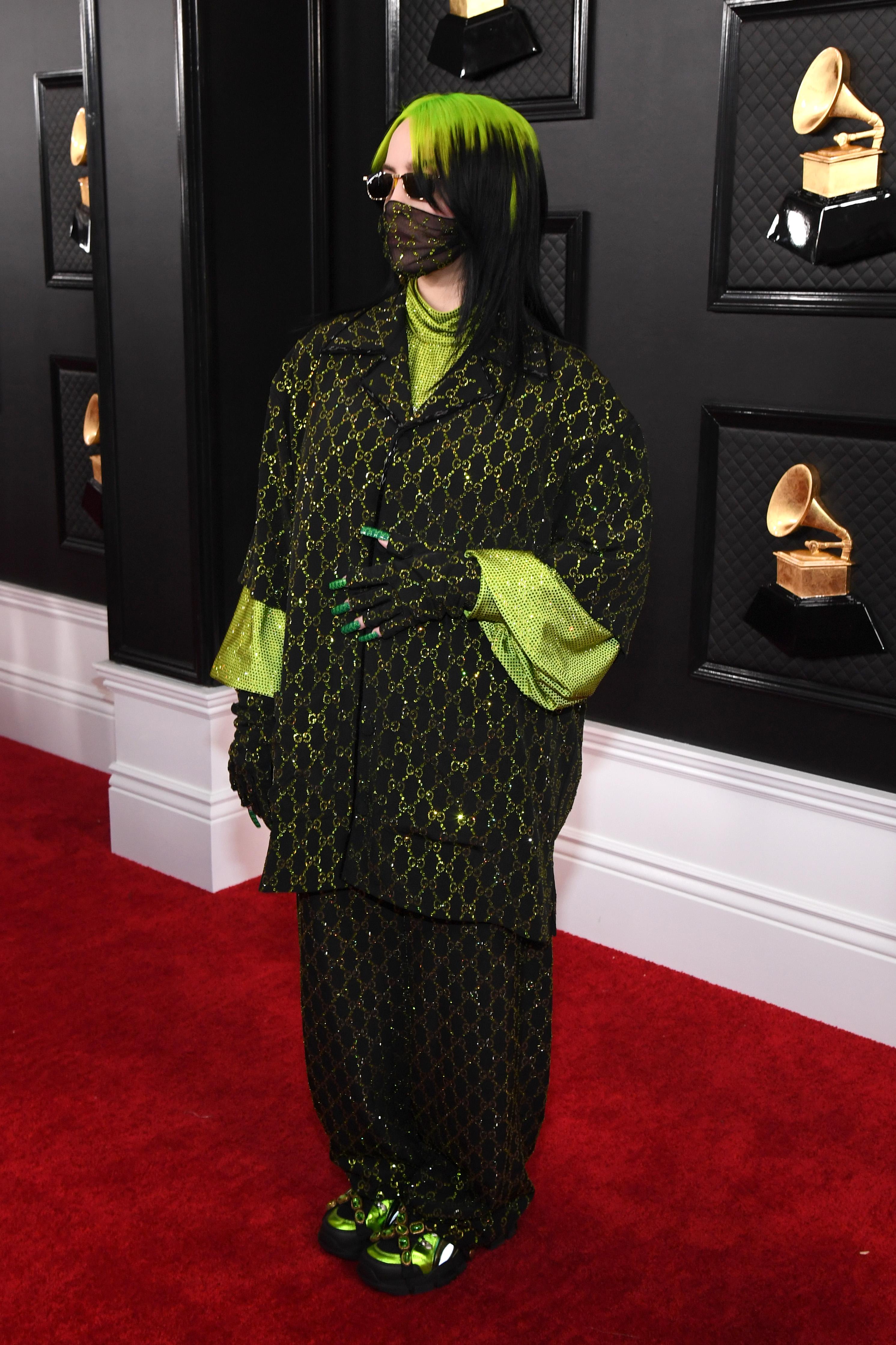 Foto da cantora Billie Eilish no tapete vermelho do Grammy Awards. Ela usa uma camisa oversized preta com detalhes verdes, calça preta com detalhes verdes e tênis preto com detalhes verdes. Ela não olha para a câmera.