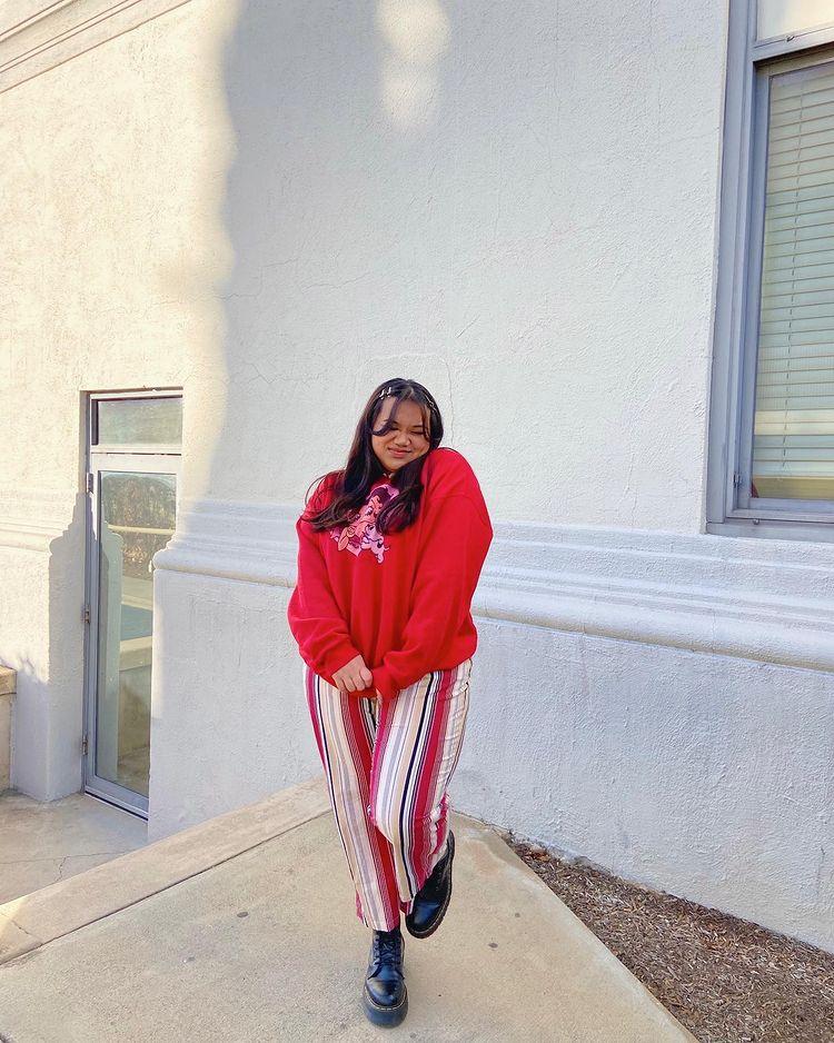 Foto de uma mulher em frente a uma casa de muro branco. Ela usa um moletom vermelho baggy, calça com listras brancas, vermelhas, pretas e bege verticais e coturno. Ela está de olho fechado e sorri para a foto.