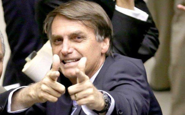Jair Bolsonaro fazendo arma com a mão