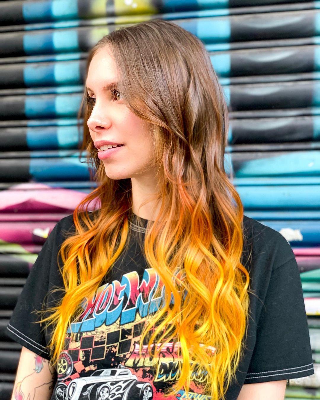 Mulher de perfil olhando para a direita. Ela está vestindo uma camiseta preta com uma estampa de letras coloridas, cabelo solto, ondulado e com as pontas amarelas