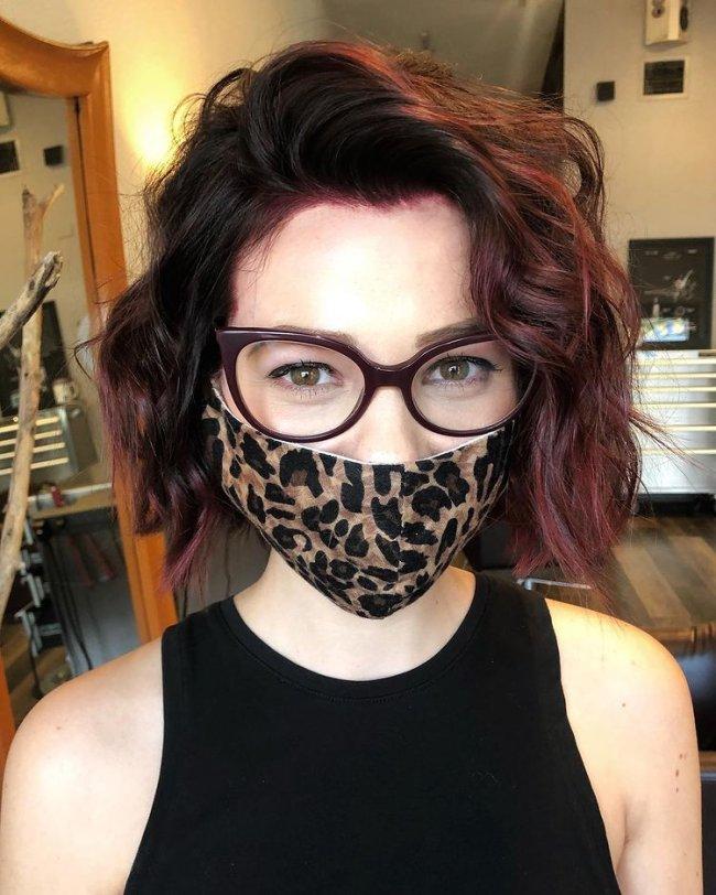 Jovem com cabelo curto e levemente vermelho, com máscara de proteção com estampa de oncinha, usando regata preta.