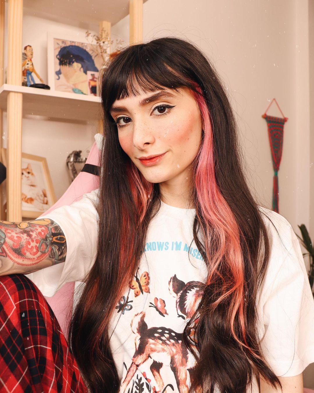 Selfie de uma mulher. Ela está vestindo uma camiseta branca com estampa de borboleta, calça com estampa xadrez preta e vermelha, cabelo preto com franja solto e com mechas laterais na cor rosa pastel. A mulher sorri para a câmera.