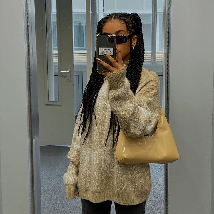 Foto de uma mulher na frente do espelho. Ela está usando calça preta, casaco de frio bege com marrom, bolsa bege e cabelo com tranças preso em um penteado simples de maria chiquinha.
