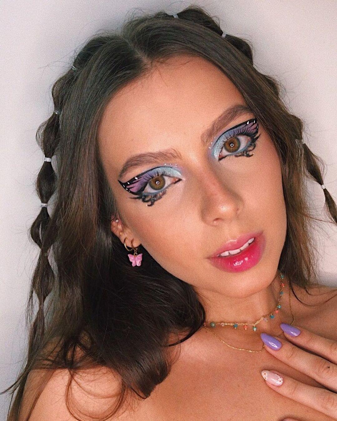 Selfie de uma mulher. Ela usa um colar dourado com pingentes coloridos, maquiagem artística de borboleta e penteado simples no estilo bolha. Ela olha para a foto mas não sorri.