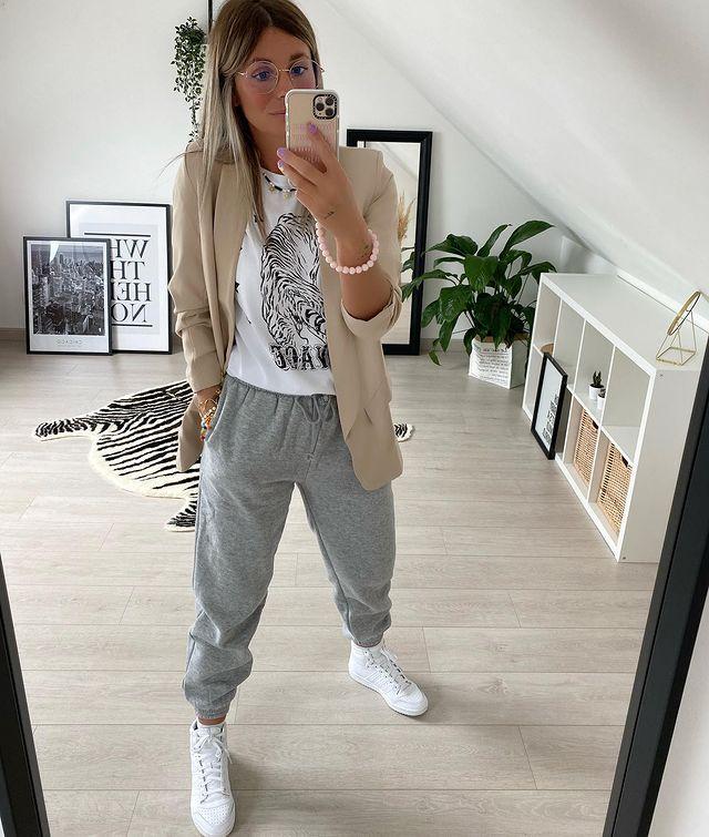Jovem posando em frente ao espelho com calça jogger cinza, camiseta branca e blazer bege.
