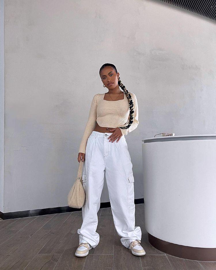 Foto de uma mulher em frente a uma parede branca. Ela usa um cropped bege de manga longa, bolsa bege, calça baggy branca e tênis. Ela olha para a câmera e não sorri.