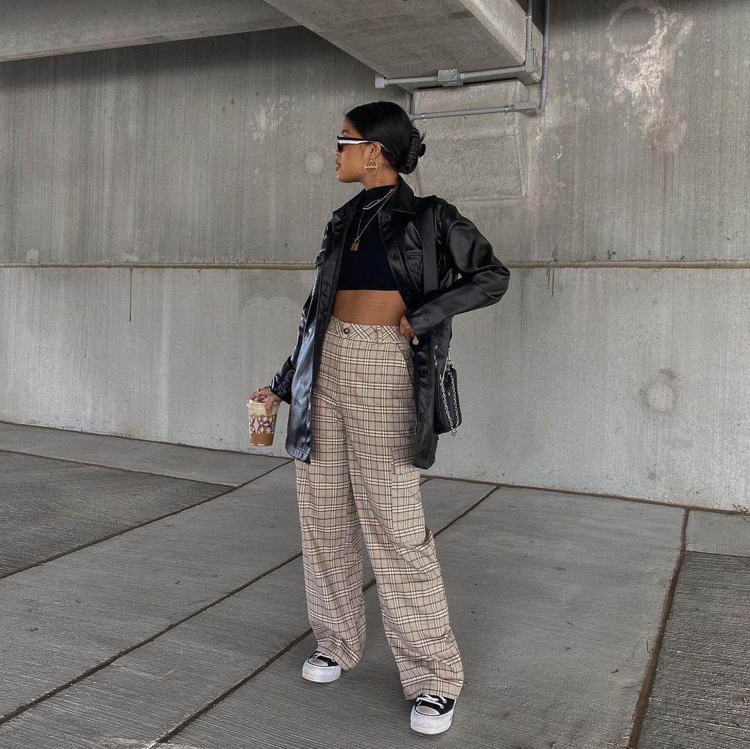 Foto de uma mulher em um estacionamento. Ela usa um cropped preto, jaqueta de couro preta, calça xadrez branca com marrom, tênis preto e bolsa preta. Ela olha para o lado e segura um copo de café.