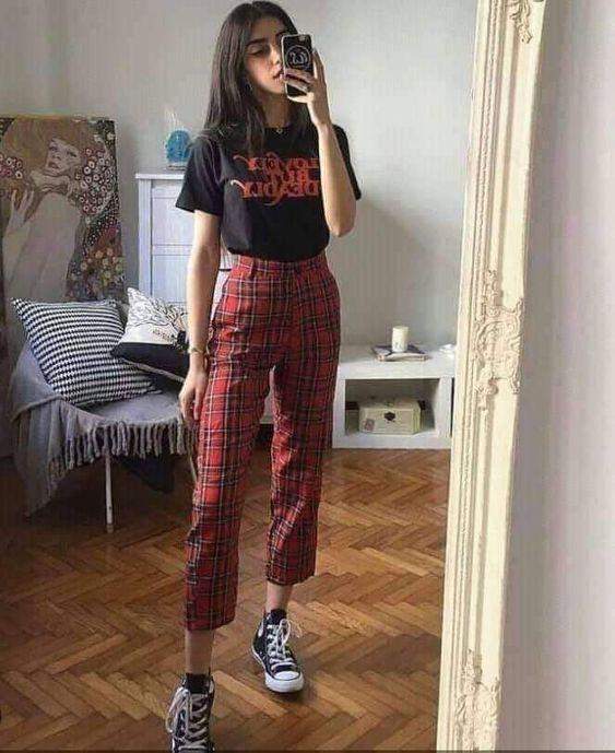 Selfie em um espelho de uma mulher. Ela usa uma camiseta preta estampada, calça xadrez nas cores vermelho e preto e tênis preto de cano alto.