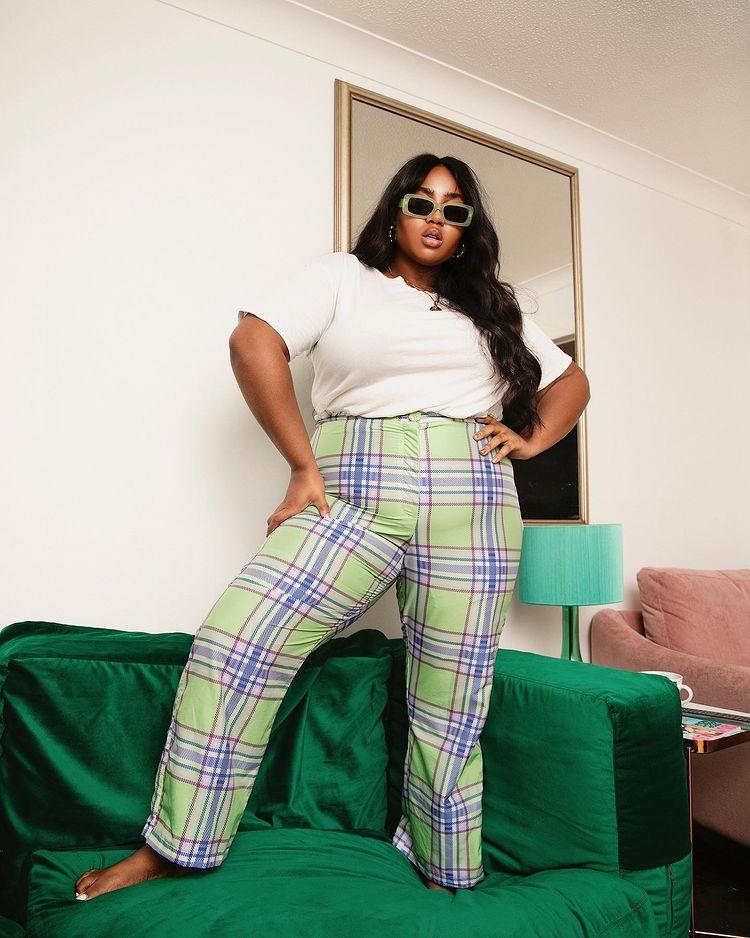 Foto de uma mulher em cima de um sofá verde em uma sala de estar. Ela usa uma camiseta branca, calça xadrez com detalhes verdes, azuis e rosa e óculos de sol. Ela está com as mãos na cintura, olha para a câmera e não sorri.