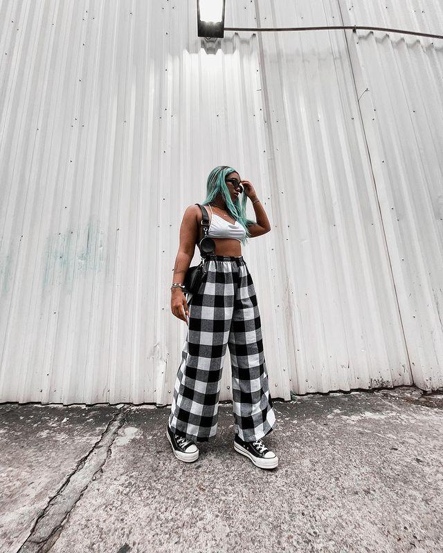 Foto de uma mulher na calçada. Ela usa um top cropped branco, calça xadrez nas cores preto e branco. Ela olha para o lado e não sorri.