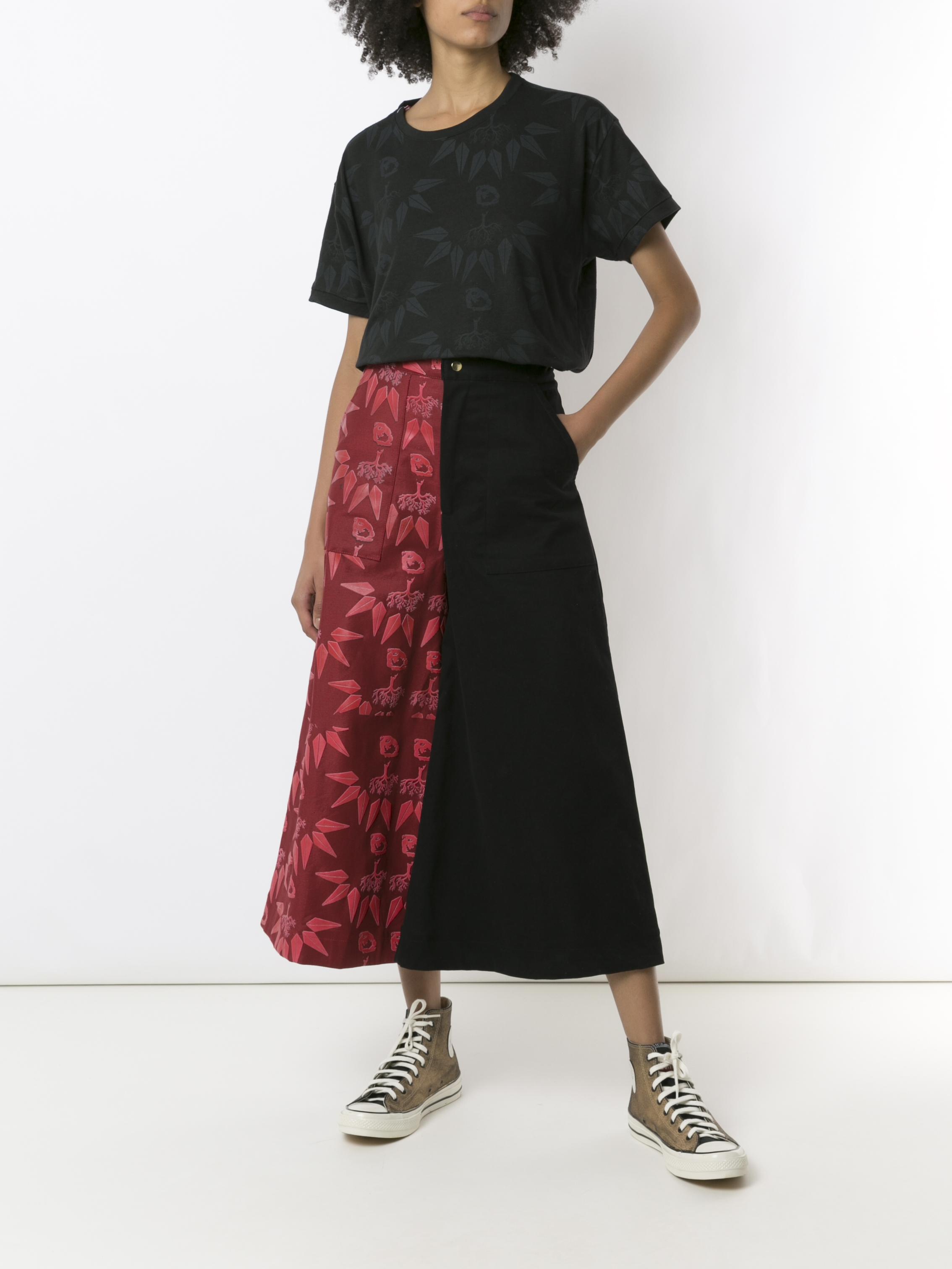 Modelo usando camiseta feita pela ONG Orientavida que faz parte da coleção Realeza, inspirada no filme Pantera Negra. A camiseta é preta e está combinada com uma saia midi preta e vermelha e tênis All Star. A modelo está com uma das mãos no bolso.