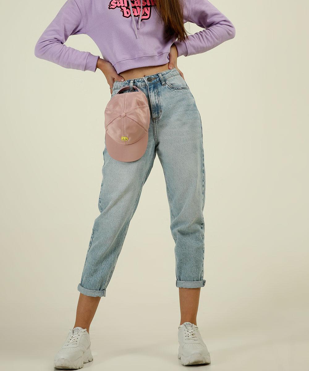 Garota usando calça mom jeans da coleção da CAPRICHO com a MARISA. Tem um boné rosa pendurado em um dos passadores da calça, ela está de tênis branco e dá para ver um pedaço do moletom lilás. Suas duas mãos estão na cintura.