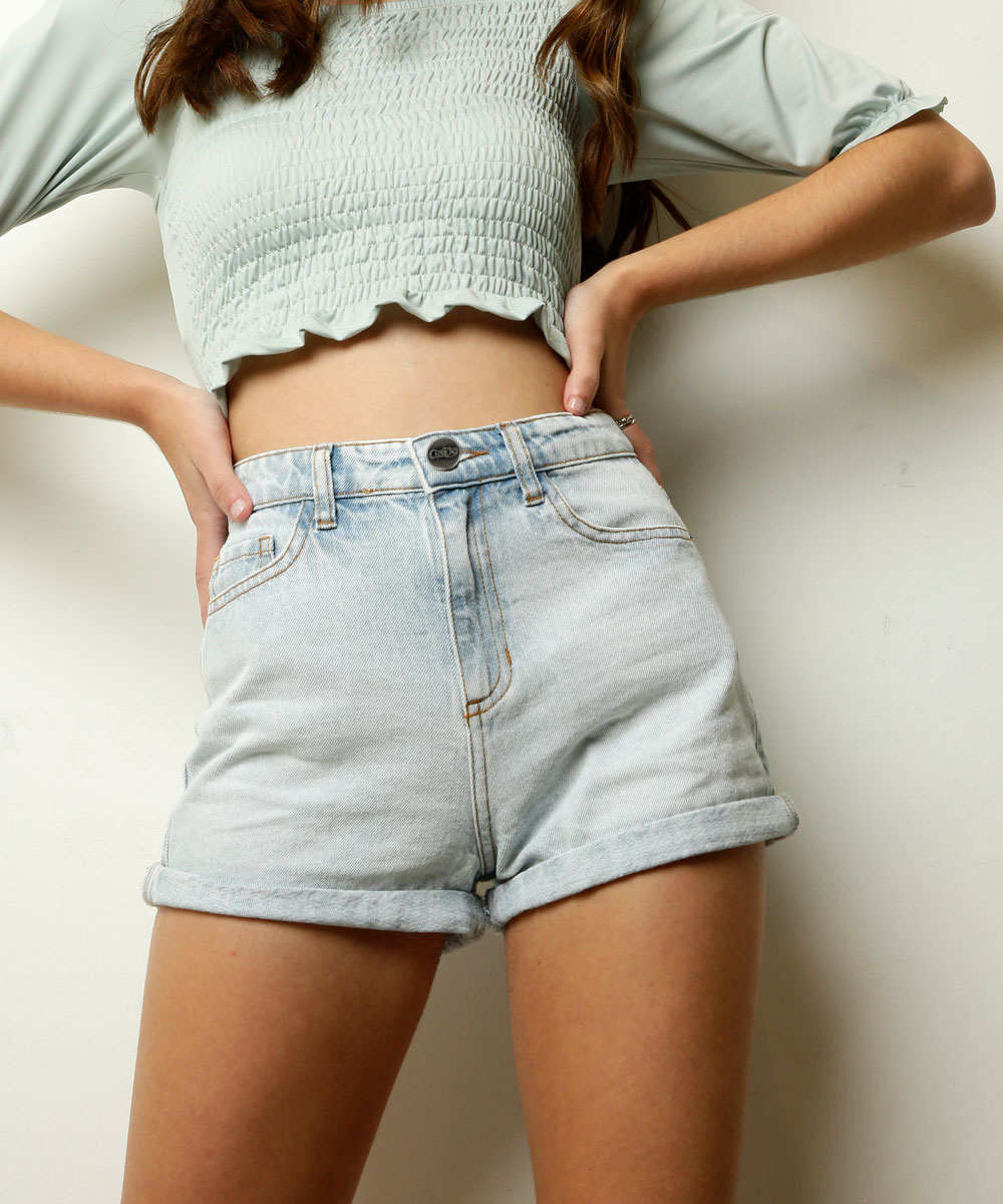 Garota usando short jeans cintura alta da coleção da CAPRICHO com a MARISA e também dá para ver o top cropped verde na foto. Ela está com as duas mãos na cintura e a foto está centralizada no short.