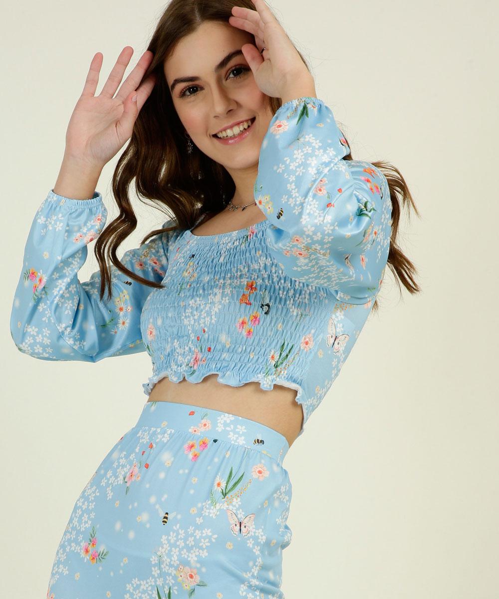 Garota usando blusa cropped de manga longa com estampa floral e fundo azul da coleção da CAPRICHO com a MARISA. Ela também está usando a saia, que só dá para ver uma parte, na mesma estampa. Ela está com as duas mãos no cabelo e sorrindo.