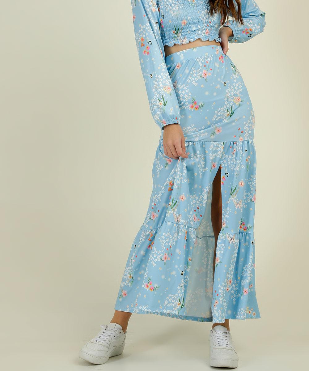 Garota usando saia longa floral com fenda da coleção da CAPRICHO com a MARISA com tênis branco. Na foto, só dá para ver da cintura para baixo. Ela está com uma das mãos na cintura, e a outra segurando a saia.