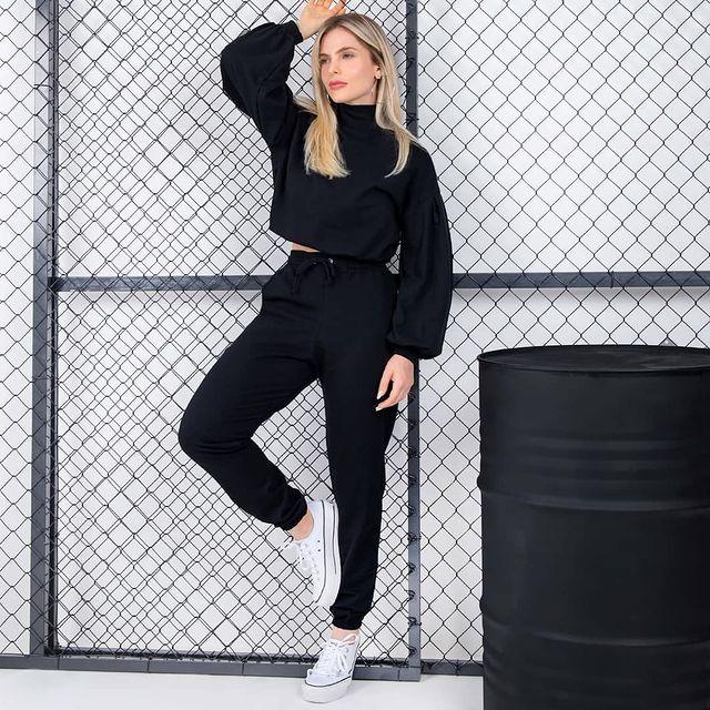 Jovem posando com expressão séria, um dos braços levantados usandoLook monocromático all black com calça jogger