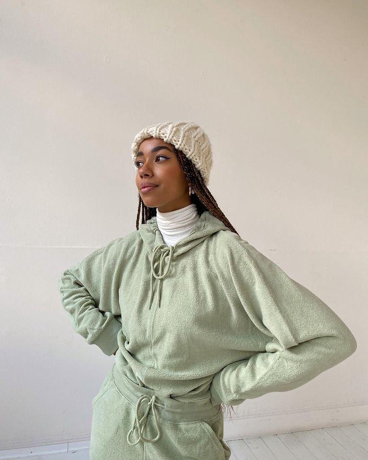 Foto de uma mulher em frente a uma parede branca. Ela usa um conjunto de moletom oversized na cor verde menta, uma blusa branca de gola alta por baixo e uma touca de tricô branca. Ela está com as mãos na cintura, olha para o lado e sorri.