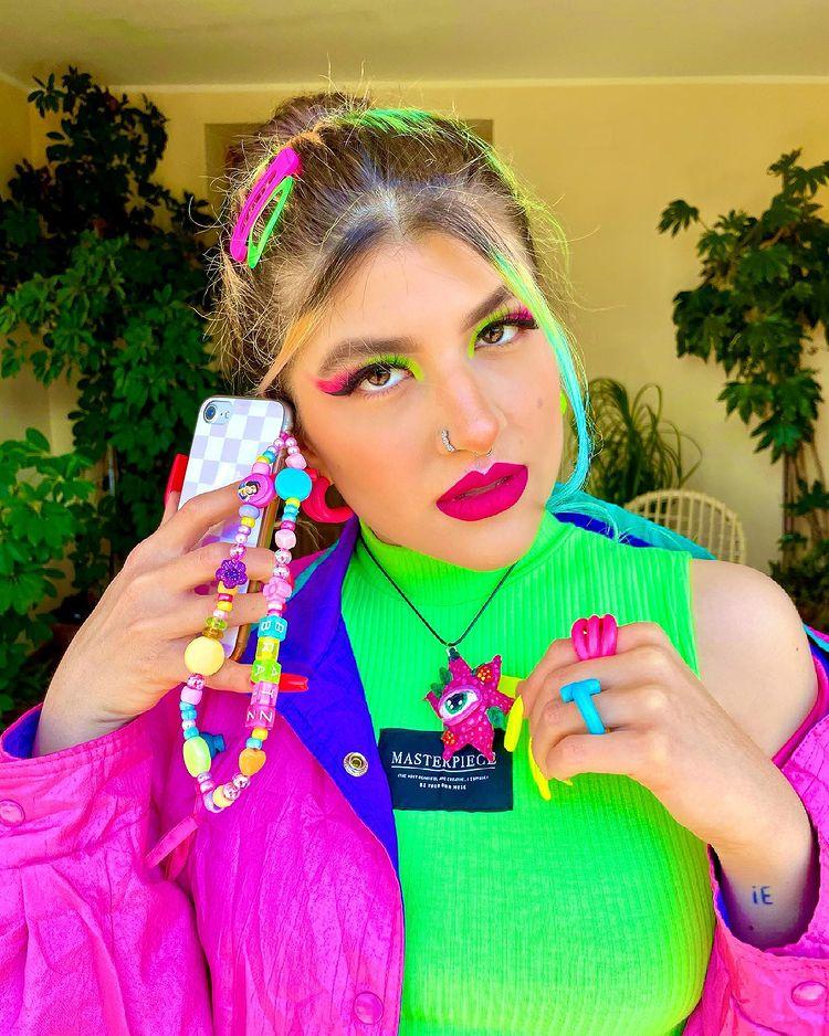 Garota usando top cropped verde neon e jaqueta roxa e azul. Ela está segurando seu celular, que tem uma cordinha de miçangas pendurada, perto da orelha, e sua expressão facial é séria. Sua maquiagem é verde neon e rosa, seu cabelo está preso e há presilhas rosa e verde neon na cabeça.