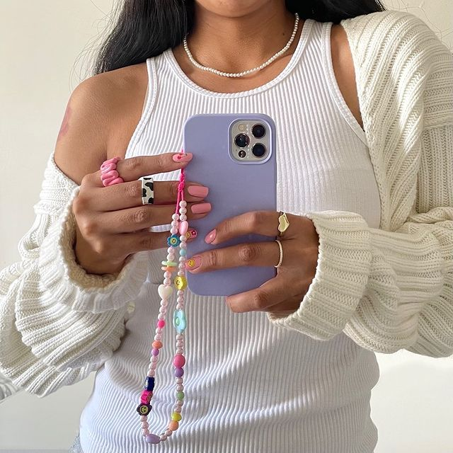Garota usando regata branca, cardigan off white e tirando foto na frente do espelho segurando o celular que tem uma cordinha de miçangas pendurada. Na foto, só dá para ver da cintura até a altura do pescoço.