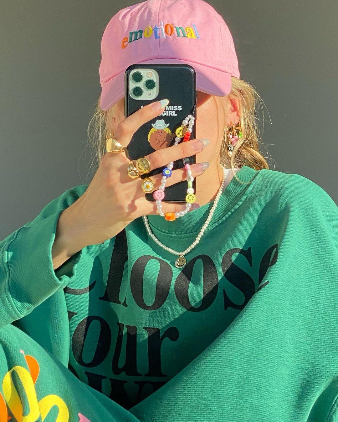 Garota usando boné rosa, moletom verde enquanto tira foto em frente ao espelho. Ela está cobrindo o rosto com seu celular, que tem uma cordinha de miçangas pendurada.