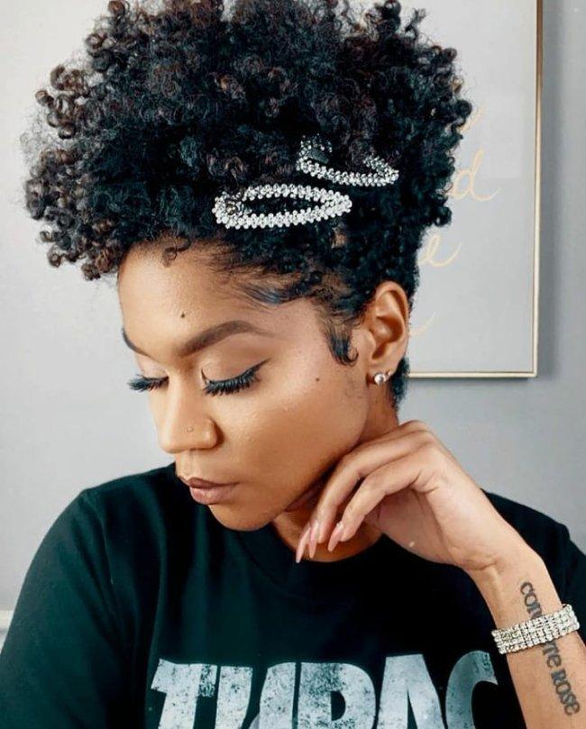 Jovem posando olhando para baixo, com duas presilhas pratas na lateral do cabelo, com uma das mãos apoiadas no pescoço, usando camisa preta.