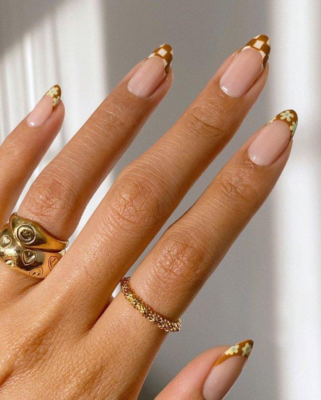 Foto de uma mão com anéis dourados no dedo anelar e indicador. A unha está com uma nail art xadrez com francesinha na cor caramelo e branco.